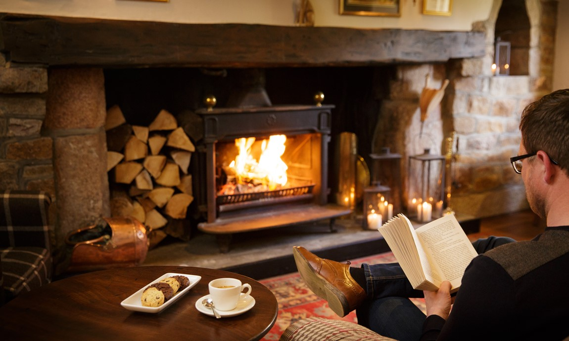 Reading by the fire in the cosy lounge